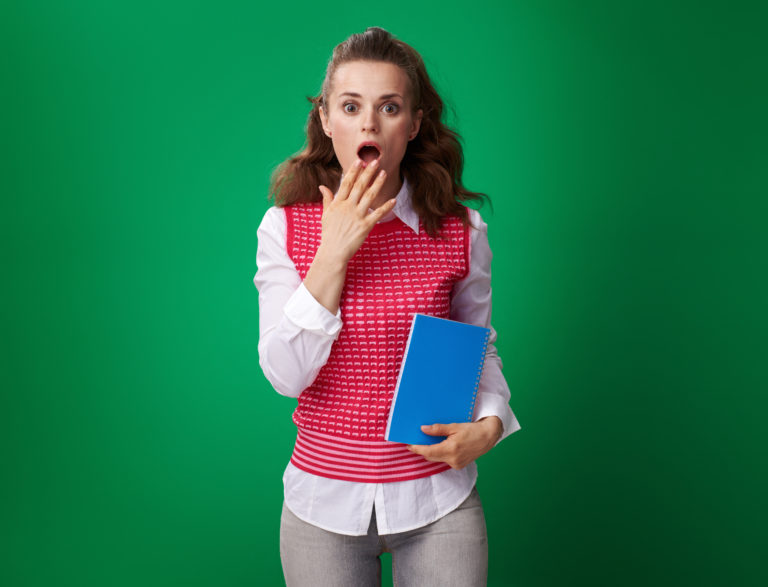 shocked modern student woman in a red waistcoat with a blue notebook isolated on green background